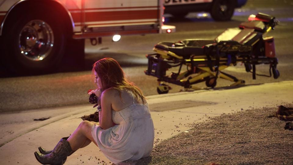 A woman sits on a curb at the scene of a shooting outside of a music festival along the Las Vegas Strip, Monday.