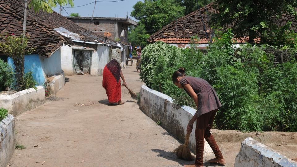 Villagers cleaning roads near their houses in model village Baghuvar in Narsinghpur district  of  Madhya Pradesh.