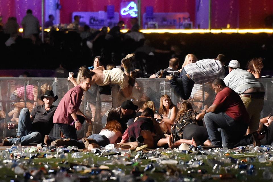 People scramble for shelter at the Route 91 Harvest country music festival after a gunman opened fire at a Las Vegas  hotel late Sunday evening.