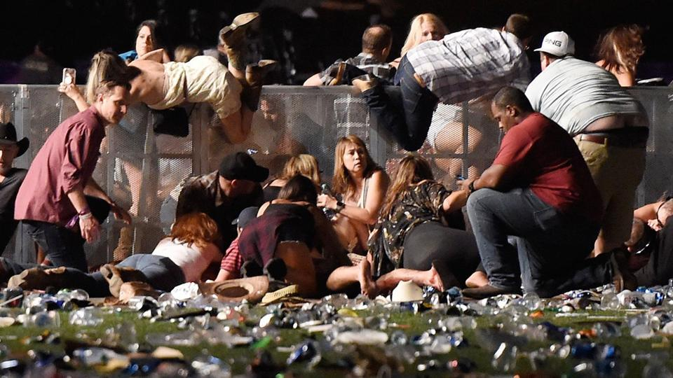 People scramble for shelter at the Route 91 Harvest country music festival after apparent gun fire was heard on Sunday in Las Vegas, Nevada. (David Becker / AFP)