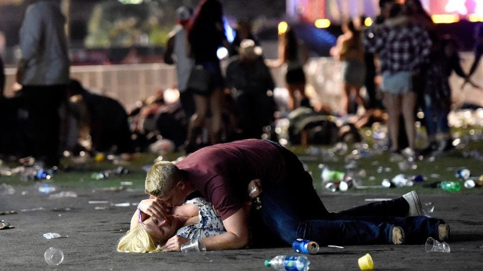 A man lays on top of a woman as others flee the Route 91 Harvest country music festival grounds during the mass shooting. The rampage was reminiscent of a mass shooting at a Paris rock concert in November 2015 that killed 89 people, part of a wave of coordinated attacks by Islamist militants that left 130 dead.  (David Becker / AFP)