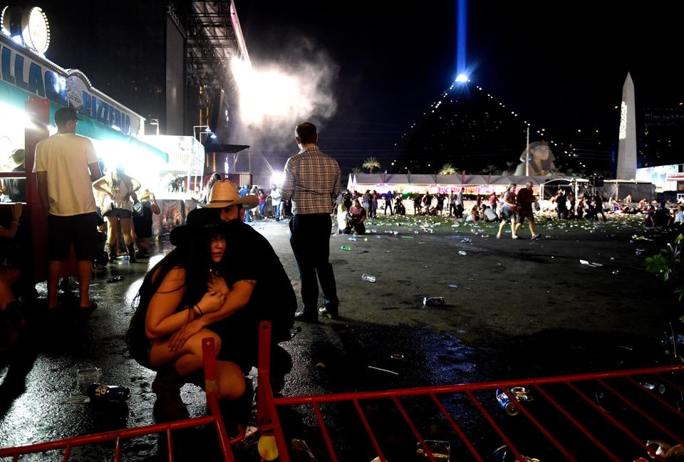People take cover at the Route 91 Harvest country music festival after apparent gun fire was heard on October 1, 2017 in Las Vegas, Nevada.