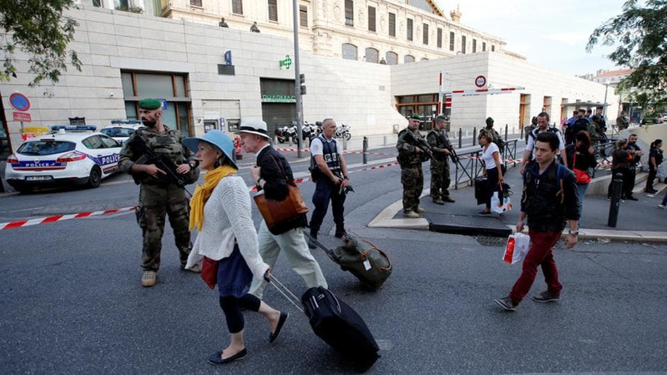Travellers walk past French police and soldiers who secure a street near the Saint-Charles train station after French soldiers shot and killed a man who stabbed two women to death at the main train station in Marseille, France, October 1.