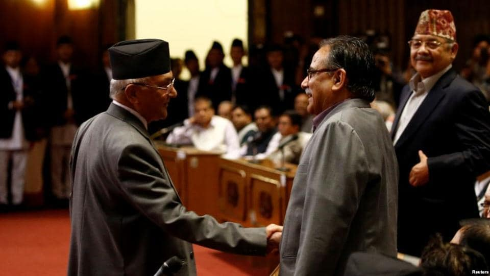 "File photo of Nepal's former premier KP Oli shaking hands with CPN-Maoist Centre leader Pushpa Kamal Dahal ""Prachanda"" (right) after announcing his resignation in parliament in July 2016."