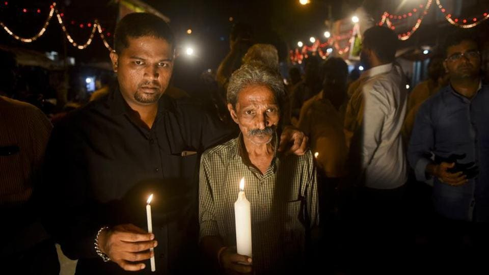 The father (right) of Mayuresh Haldankar, one of the victims of last Friday's Elphinstone Road stampede, participates in a candle light vigil at the station on Monday.