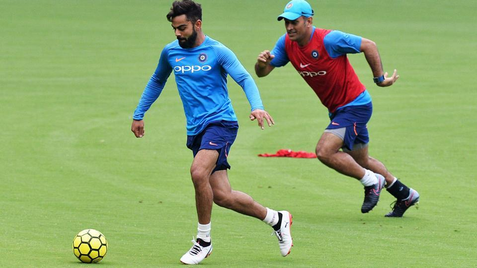 Indian cricket team captain Virat Kohli (L) and teammate MS Dhoni play football during a practice session. Kohli has wished good luck to the Indian FIFA U-17 World Cup squad.