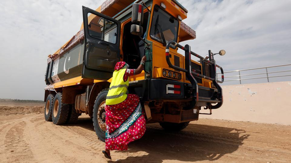 Gulaban, 25, seen climbing onto a 60-tonne truck to drive it in Islamkot, Pakistan. Many women are training to be truck-drivers as the vehicles are used in Thar desert for mining, while Pakistan bets on cheap coal to resolve its energy crisis.  (Akhtar Soomro / REUTERS)