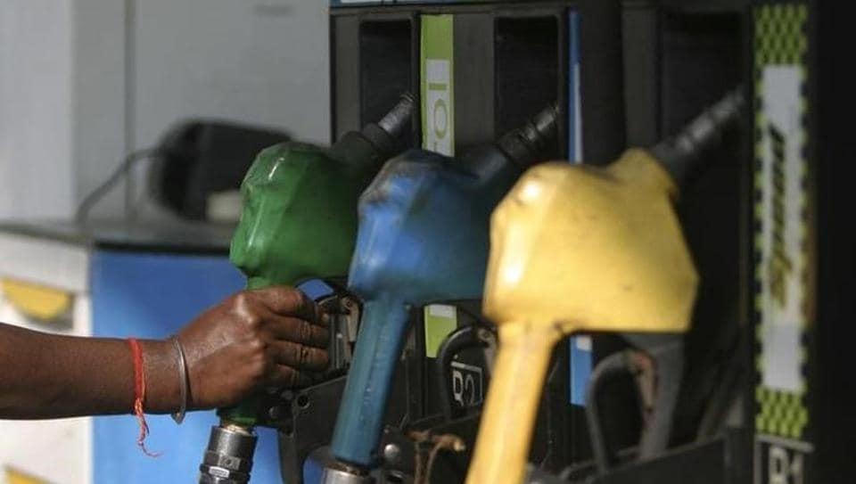 An attendant lifts a petrol nozzle at a petrol pump in Siliguri.