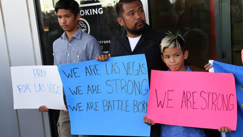 Jon Dimaya (C) of Nevada, a rapid response team nurse at Sunrise Hospital & Medical Center, and his sons Ethan Dimaya (L) and Gryffin Dimaya (R) hold signs during a prayer vigil outside Las Vegas City Hall in response to Sunday's mass shooting on October 2.