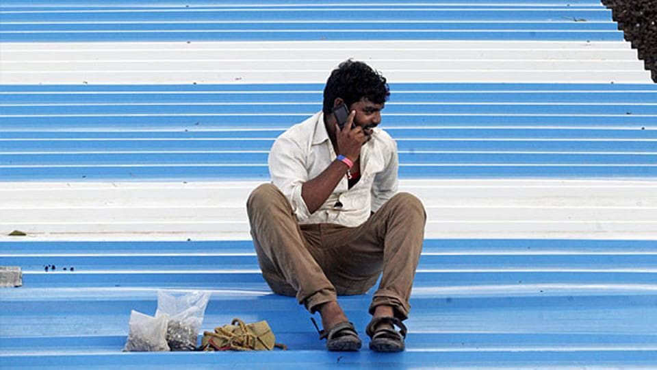 A railway worker sits on the roof of a platform and talks on the phone while carrying out maintenance work, at Mumbai Central.