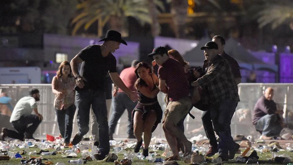 People carry a person at the Route 91 Harvest country music festival after gun fire in Las Vegas, Nevada.