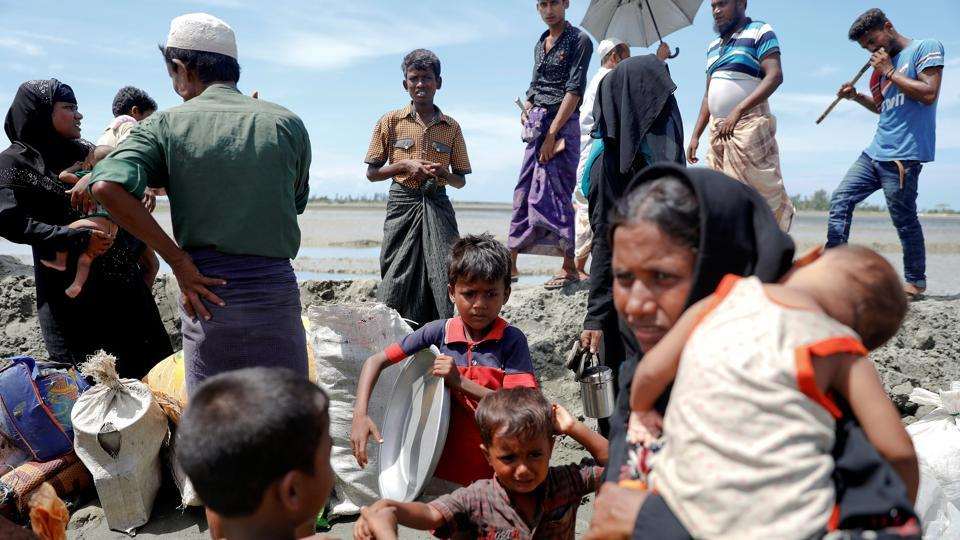 Rohingya refugees who arrived from Myanmar pick up their children and belongings to make their way to a relief centre in Teknaf, near Cox's Bazar, in Bangladesh on October 3, 2017.