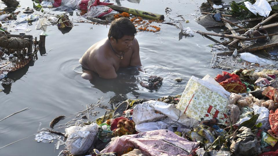 A man finding coins after immersion of Durga idols after the celebration of Durga puja in the Yamuna river near ISBT in New Delhi