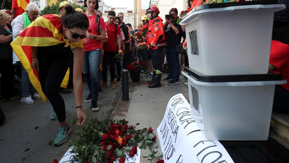 People place flowers in front of ballot boxes during a protest against police actions during the banned independence referendum in front of city hall in Pineda de Mar, north of Barcelona. (Albert Gea / REUTERS)