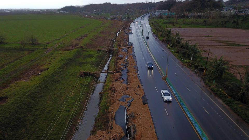 Cars drive on a highway next to downed power line poles by Hurricane Maria in Vega Alta, Puerto Rico. While the region reels in darkness, the road to rebuilding and restoring power completely across the area is expected to take atleast a month despite the financial aid from Washington.  (Ricardo  Arduengo / AFP)