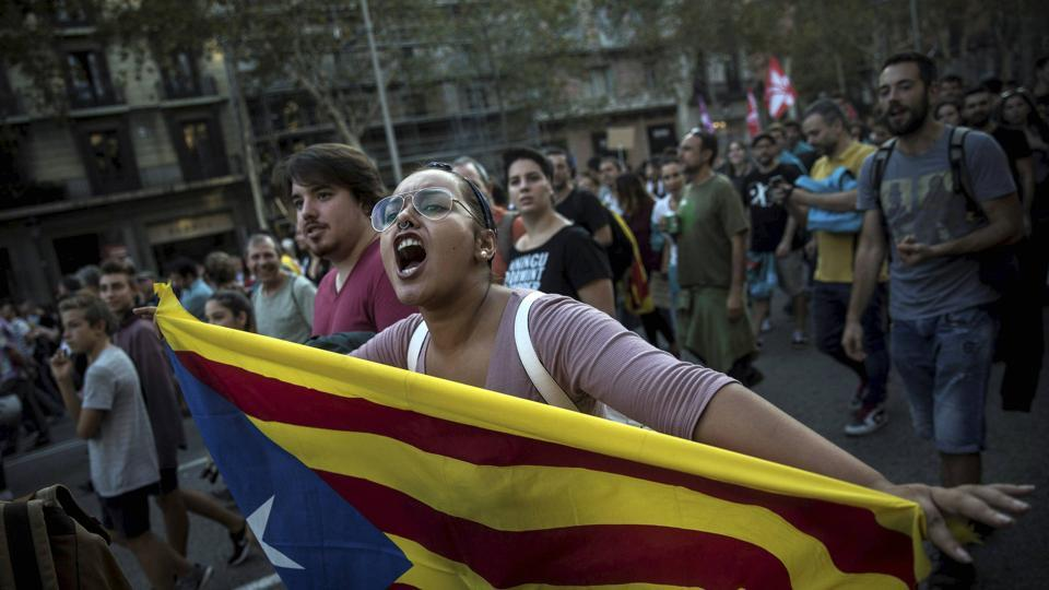 In Barcelona, a woman carries an independence Catalan flag as demonstrators marched downtown.  (PTI / AP)