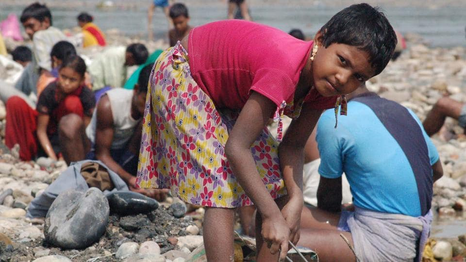 A slum girl searches for valuable items on the Ganga bank in Haridwar.