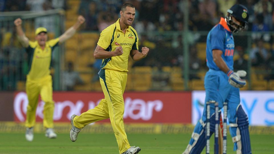 Australia cricket team bowler Nathan Coulter-Nile celebrates after bowling out Indian cricket team captain Virat Kohli (R) during the fourth ODI at M Chinnaswamy Stadium in Bangalore on September 28.