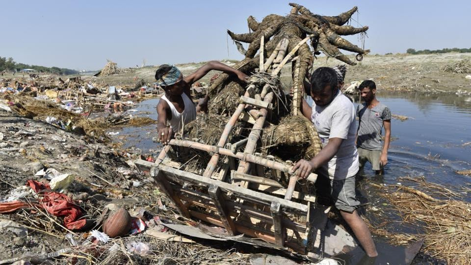Workers from flood control department remove idols from the riverbed. Child scavengers, treasure hunters and MCD's clean-up teams throng Delhi's Yamuna Ghats during the immersion period. Some look for remains of idols for resale and reuse, others hunt for jewellery and coins in the debris. (Sanchit Khanna / HT PHOTO)