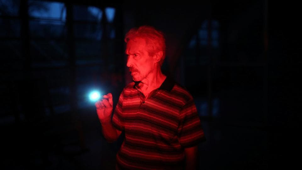 A man uses a flashlight at the Moradas Las Teresas Elderly House, where about two hundred elderly people are  living without electricity following damages caused by Hurricane Maria. (Carlos Barria / REUTERS)