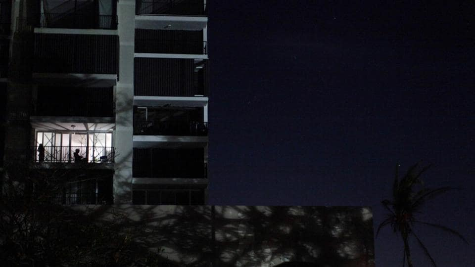 Local residents sit at their apartment's balcony as areas of San Juan are still left without electricity following Hurricane Maria in Guaynabo, Puerto Rico. Residents are without cell phone signals and fuels for their generators and cars. About 88 percent of cellphone sites are still out of service. (Alvin Baez / REUTERS)