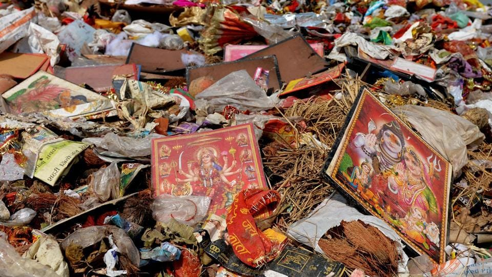 With nearly 200 Durga Puja pandals immersing idols near  Delhi-NCR, the river  water was clogged with plastic bags, flower petals and pooja material, besides metal structures. (Money Sharma / AFP)