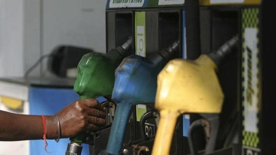 An attendant lifts a petrol nozzle at a petrol pump in Siliguri.