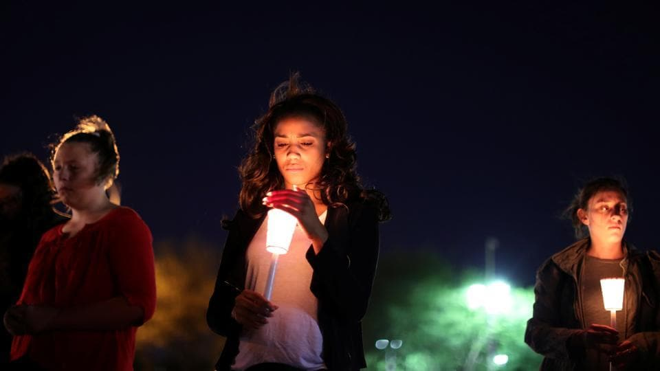 People attend a candlelight vigil for victims of the Route 91 music festival mass shooting next to the Mandalay Bay Resort and Casino in Las Vegas, Nevada.