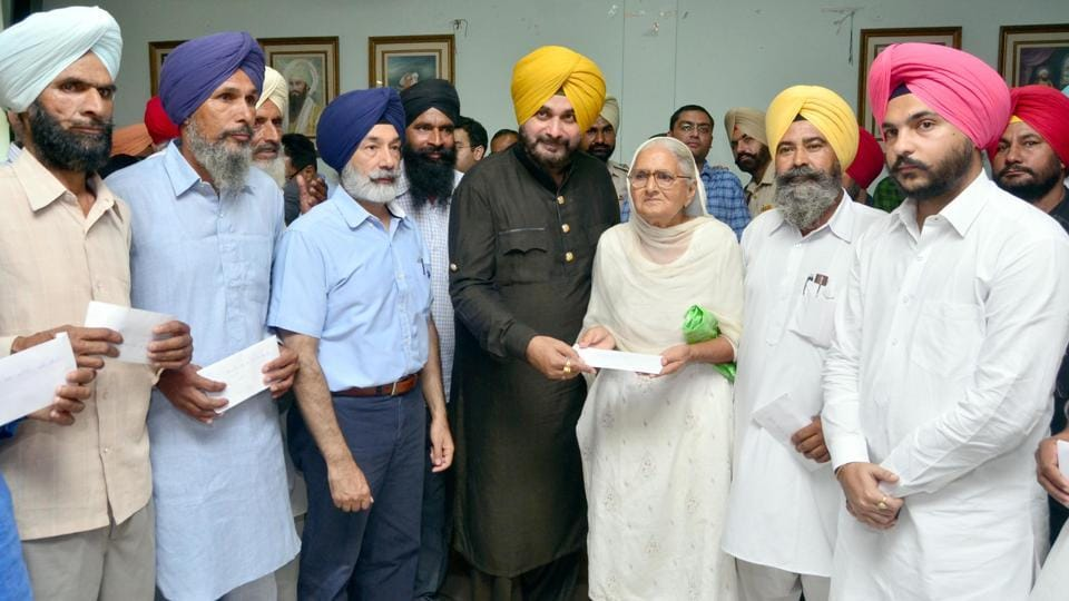 Punjab local bodies minister Navjot Sing Sidhu giving compensation to the aggrieved farmers at Bachat Bhawan, in Amritsar on Wednesday.