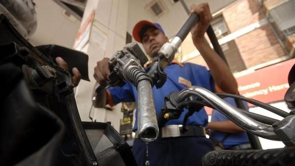 A worker holds a fuel nozzle at a petrol pump in Hyderabad. The government cut basic excise duty on petrol and diesel as global oil prices sent retail fuel rates to a three-year high.