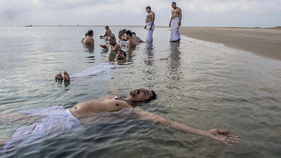 Devotees bathe in the waters of Dhanushkodi on Pamban Island, the country's closest point to Sri Lanka. Recently, a team of researchers announced their intention to conduct an underwater exploration to determine the formation of Rama Setu. (Atul Loke / NYT)