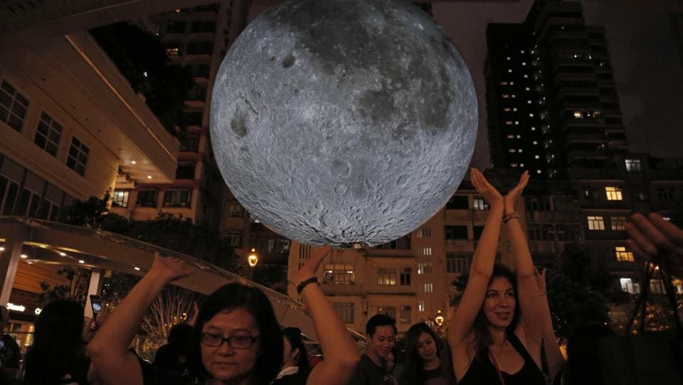 Visitors pose for photographs in front of an installation 'Museum of the Moon', a giant seven metre wide glowing sculpture of the moon, created by British artist Luke Jerram in Hong Kong to celebrate the Mid-Autumn Festival. Held on the 15th day of the 8th month of the lunar calendar on a full moon night, the harvest festival is also associated with traditions of moon worship and gazing.  (Kin Cheung / AP)