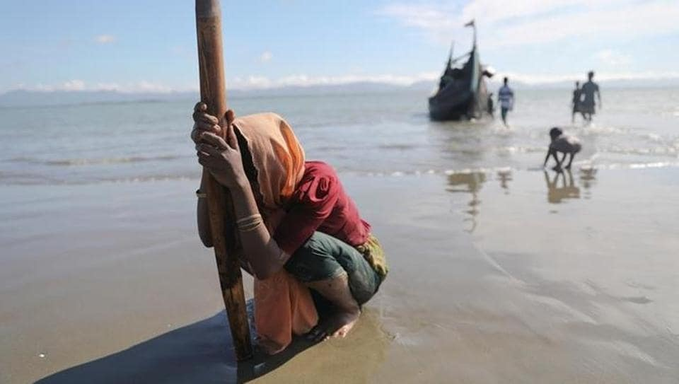 A woman collapses from exhaustion as Rohingya refugees arrive by a wooden boat from Myanmar to the shore of Shah Porir Dwip, in Teknaf, near Cox's Bazar in Bangladesh on October 1.