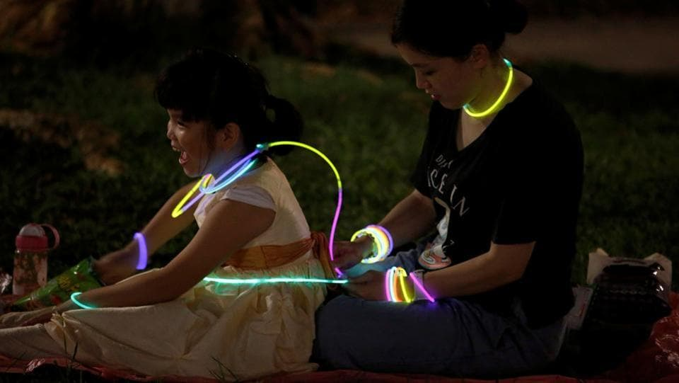 Residents play with glow sticks as they celebrate Mid-Autumn or Lantern Festival at a park in Hong Kong. (Bobby Yip / REUTERS)