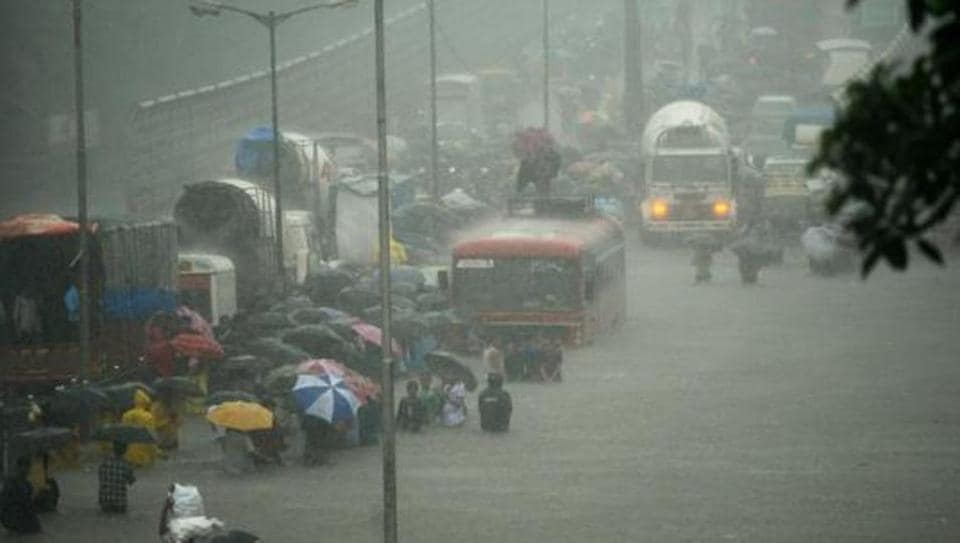 People wade along a flooded street during heavy showers in Mumbai on August 29, 2017. The rain brought the financial capital to a virtual standstill on August 29, flooding streets, causing transport chaos and prompting warnings to stay indoors.