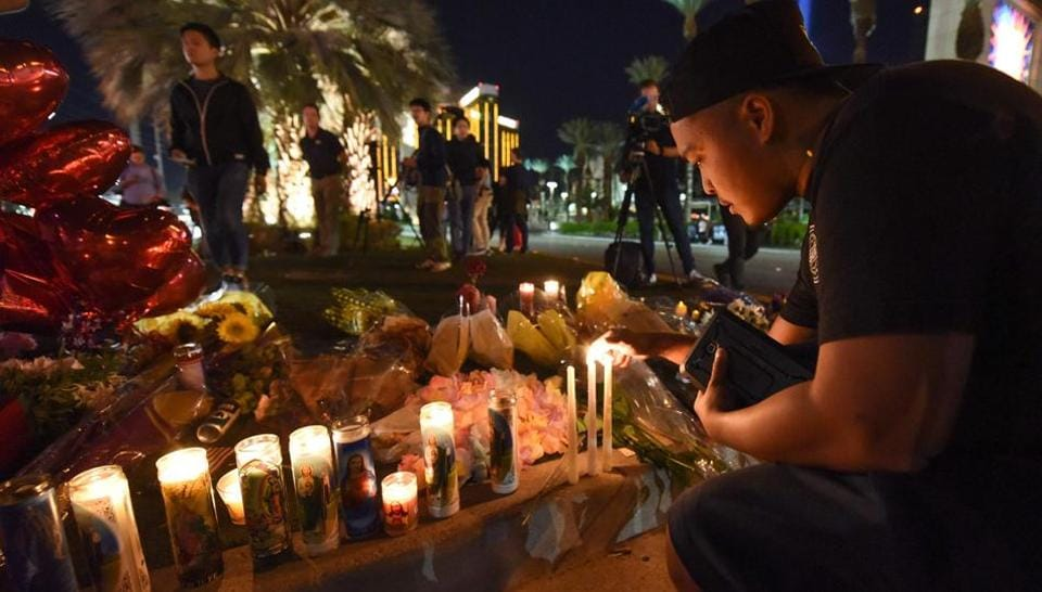 Man lights candles at a makeshift memorial near the Mandalay Hotel on the Las Vegas Strip, in Las Vegas, Nevada on October 3, 2017, after a gunman killed 58 people and wounded more than 500 others, before taking his own life, when he opened fire from a hotel on a country music festival.