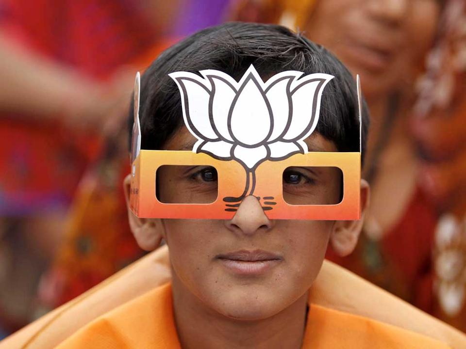 A boy wearing paper goggles featuring the Bharatiya Janata Party's symbol.