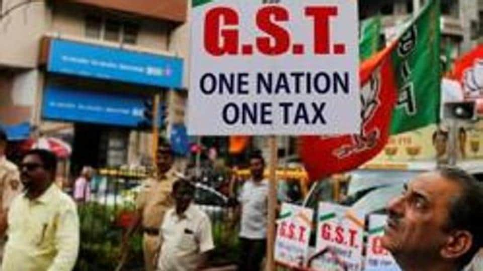 A BJP supporter of holds a placard during a rally to support implementation of the Goods and Services Tax (GST) in Mumbai.
