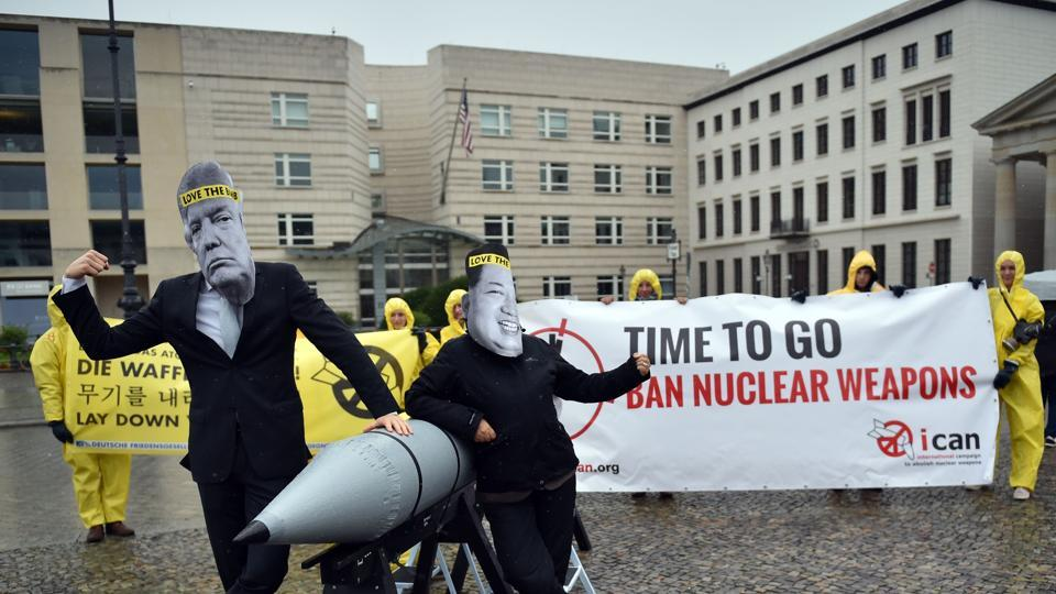Picture taken on September 13, 2017 shows activists of the International campaign to abolish Nuclear Weapons (ICAN) wearing masks of US President Donald Trump (L) and North Korea's leader Kim Jong-un as they demonstrate in front of the US embassy in Berlin. The world's nuclear powers must begin
