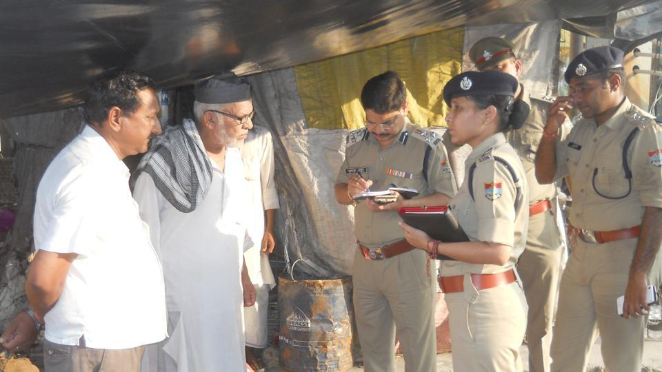 Police take inputs from locals after a few shops were torched in Rishikesh on Friday.