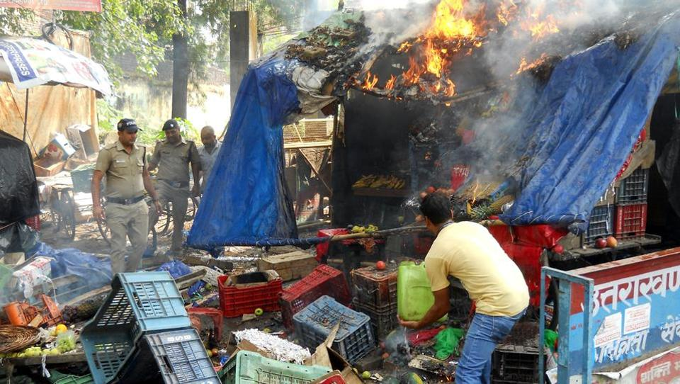 A man tries to douse fire as policemen look on after right wing activists torched a vegetable shop in Rishikesh.