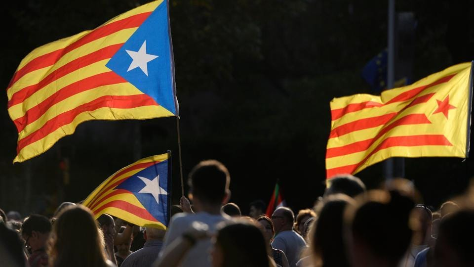 People hold Catalan pro-independence 'Estelada' flags in Barcelona during a general strike in Catalonia called by Catalan unions on October 3. Large numbers of Catalans observe a general strike to condemn police violence at a banned weekend referendum on independence.
