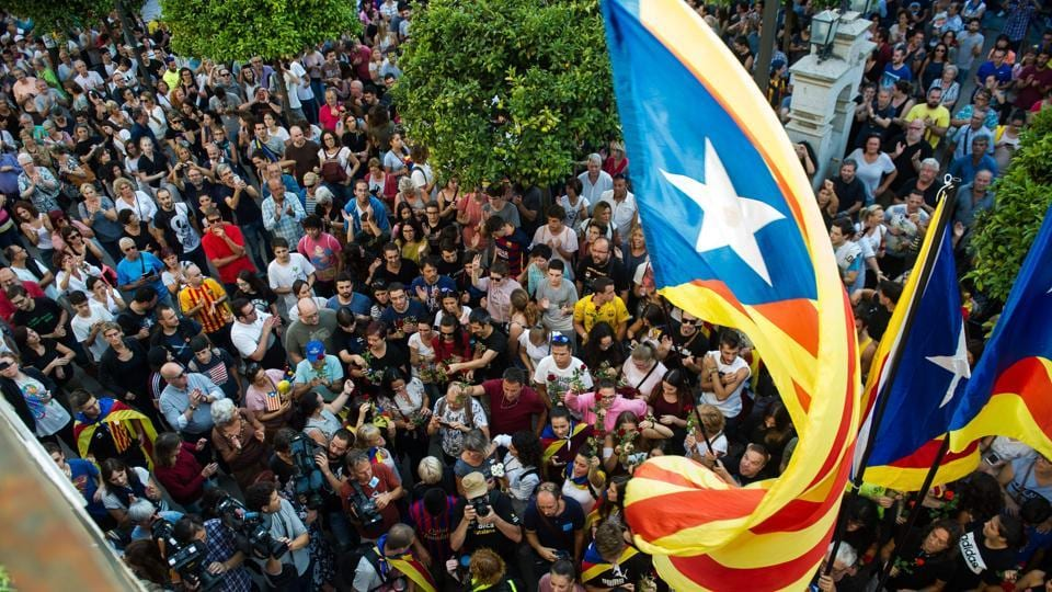 People queue to lay flowers in front of ballot boxes used during the Catalan independence referendum in Pineda de Mar, on October 3, 2017, during a general strike in Catalonia.