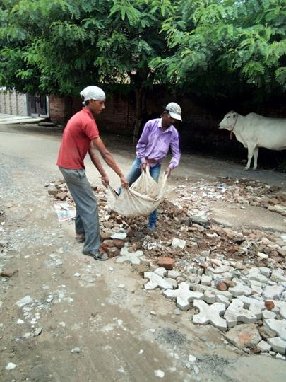 Sector 22 residents hired labourers to fill the potholes on internal roads with construction rubble.