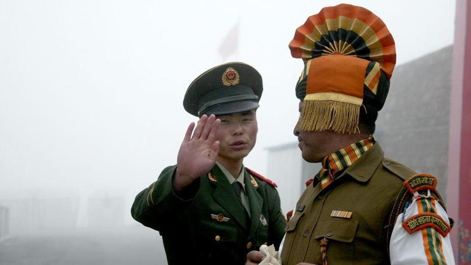 This file photo taken on July 10, 2008, shows a Chinese soldier (L) gesturing next to an Indian soldier at the Nathu La border crossing between India and China in India's Sikkim state.