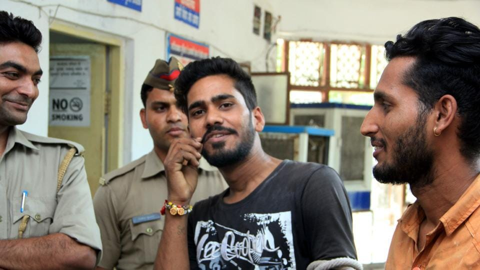 An accused poses for a picture outside the office of SP (rural) in Ghaziabad on Friday as policemen share the joke and laugh.