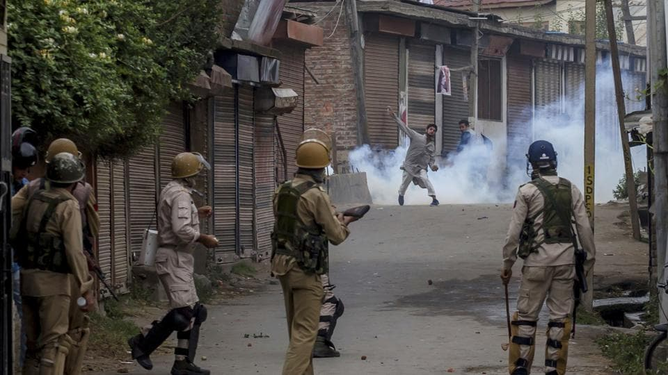 A protester throws a rock at government forces during a protest outside Eidgha in Srinagar on Sept. 2, 2017.