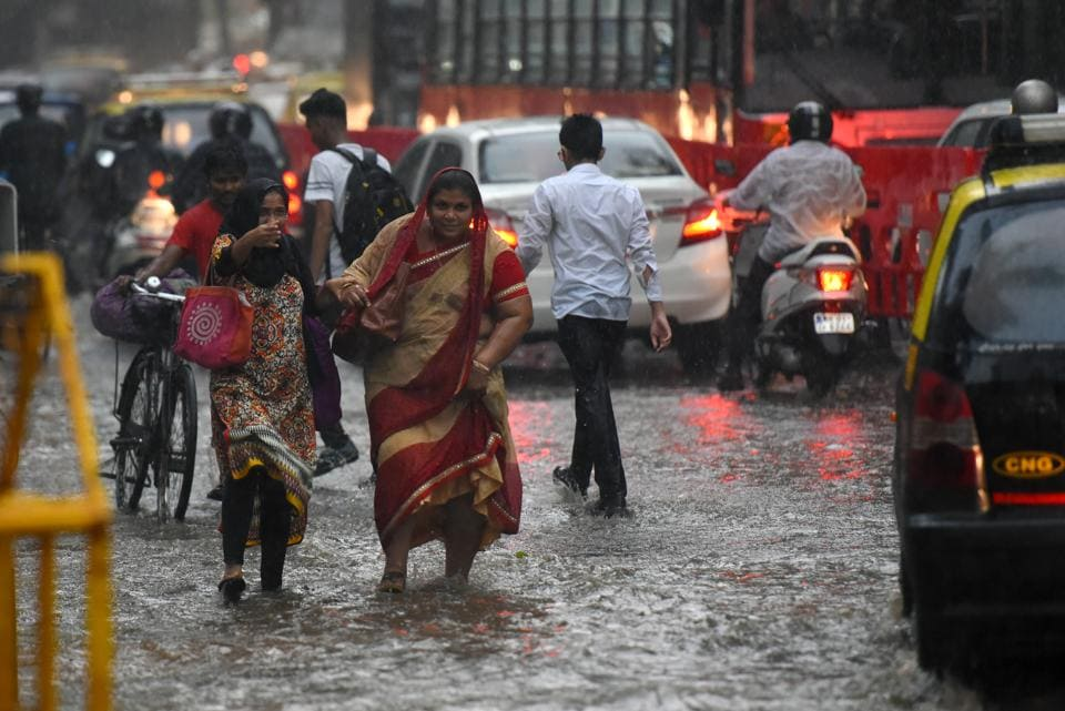 People run for cover at Mazgaon  following a sudden downpour on Friday.