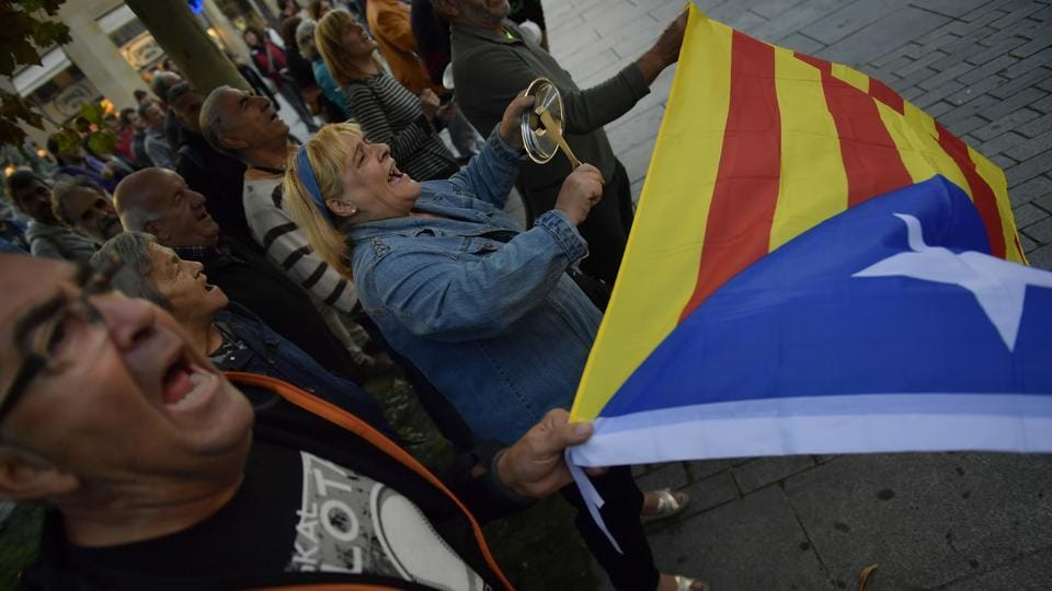 Pro-independence supporters shout slogans in front of the Popular Party headquarters as a woman holds up 'esteleda' or pro-independence flag, in support of the Catalonia's secession, in Pamplona, northern Spain, on October 6.