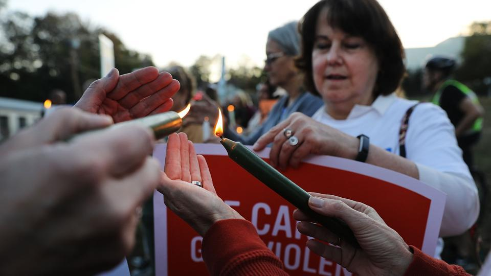 People light candles during a vigil in Newtown, Connecticut, remembering the 58 people killed in Sunday's shooting in Las Vegas on October 1.